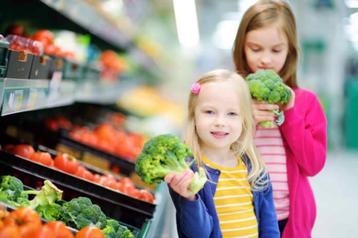 Due bambine con in mano broccoli accanto al banco degli ortaggi di un supermercato
