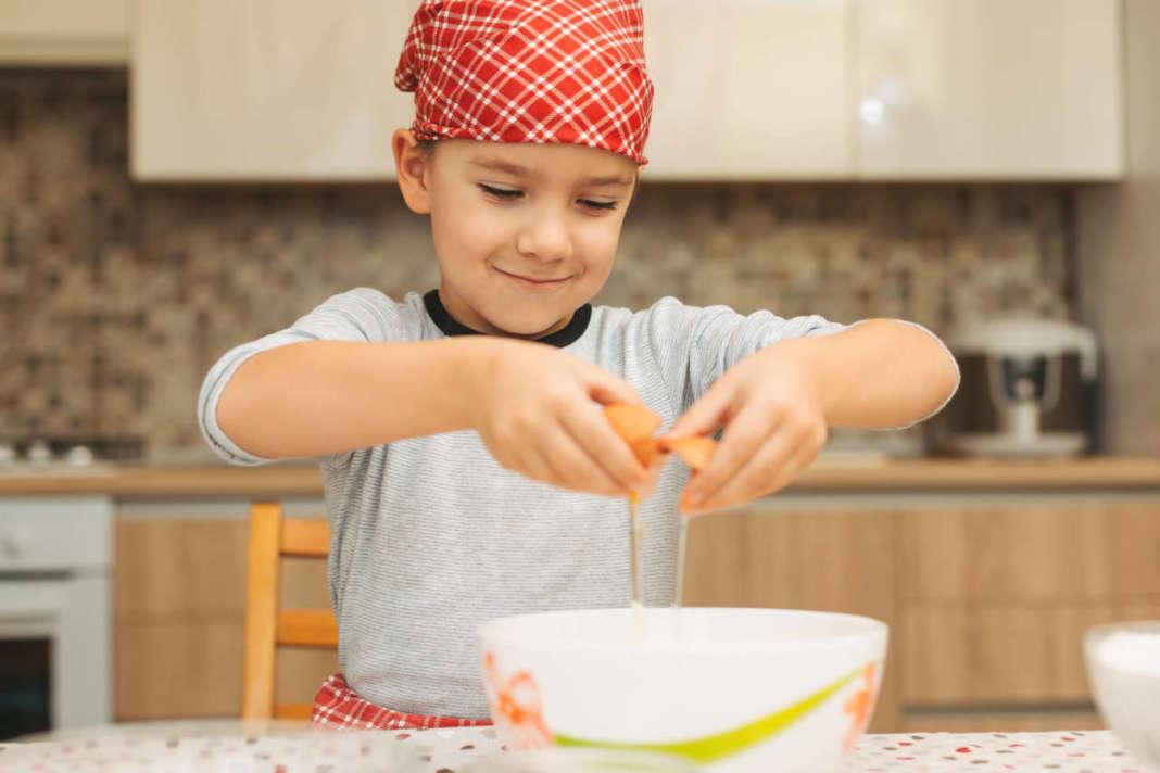 Bambino che rompe un uovo in una ciotola
