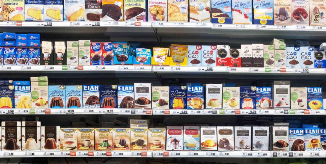 scaffale del supermercato con confezioni di creme e budini
