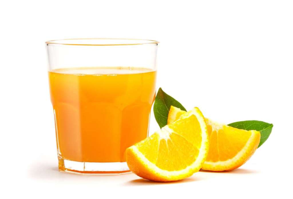Bicchiere con arancia e spicchi d'arancia