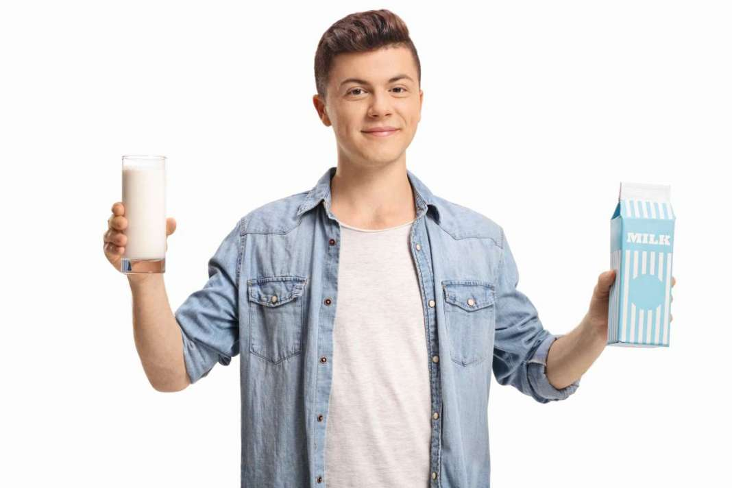 ragazzo con in mno cartone del latte e un bicchiere di latte