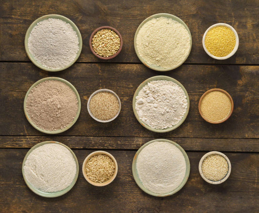 Collection of gluten free grain and flours in small bowls. Left from top buckwheat, teff, rice. Right from top millet, amaranth, quinoa