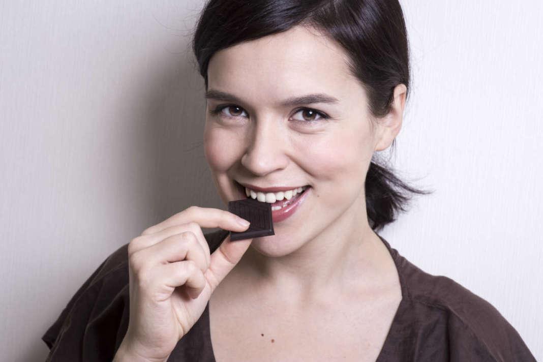 giovane donna che mangia cioccolato fondente