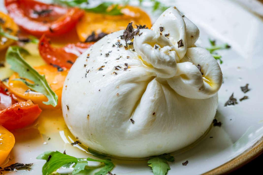 Burrata nel piatto con contorno di peperoni