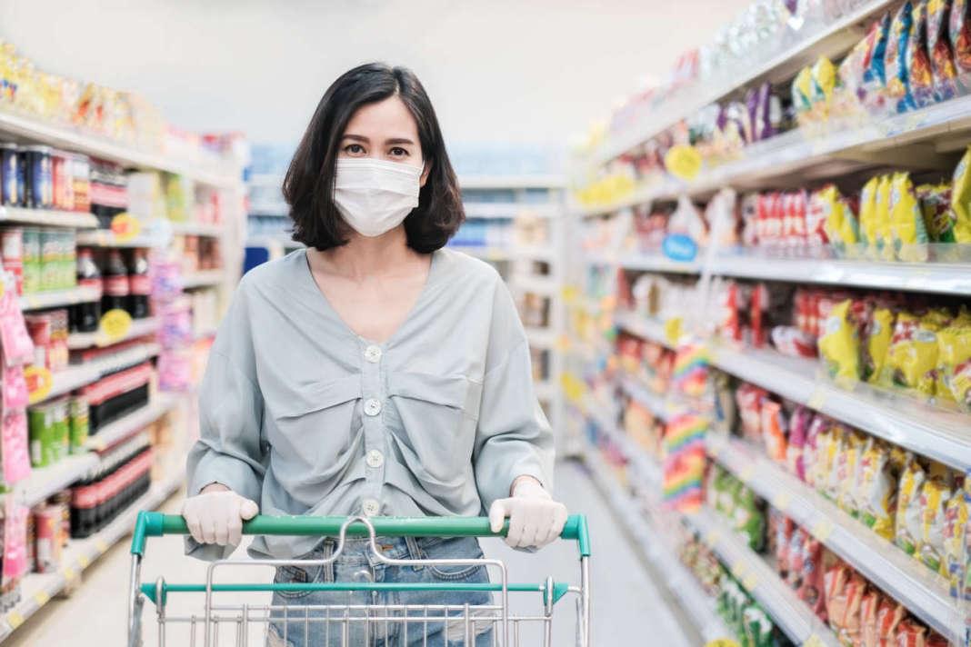 donna al supermercato con carrello, con maschera e guanti protettivi anti covid