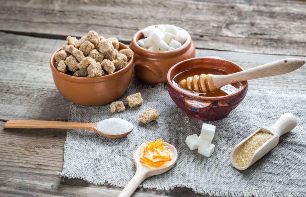 ciotole e cucchiai di legno con zucchero e altri dolcificanti