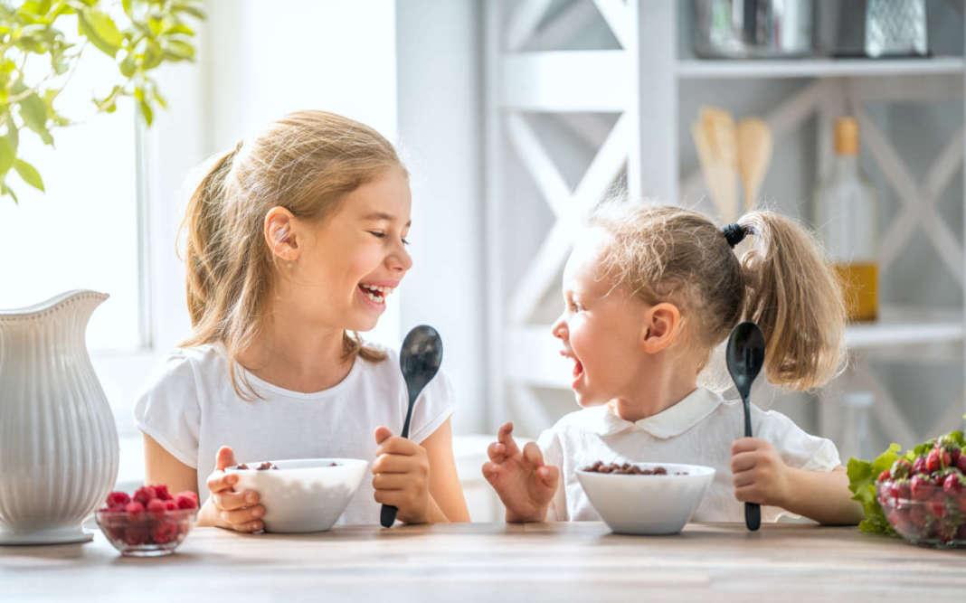 due bambine sorridenti mangiano cereali per la colazione