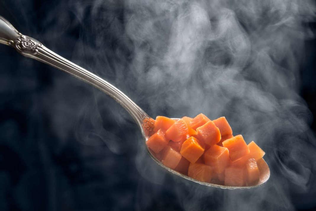 cucchiaio che contiene cubetti di carota cotti con la cucina a vapore